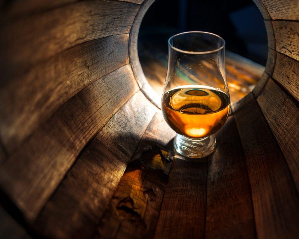 A glass of whisky inside an empty barrel