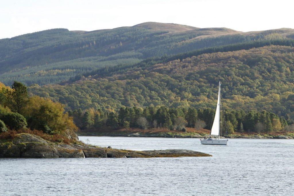 A boat cruises around the Isle of Bute in Scotland
